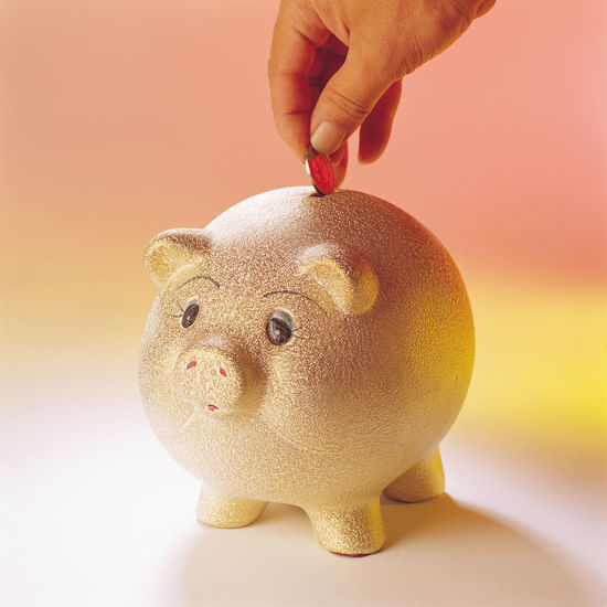 Cropped hand putting coin in piggybank over colored background