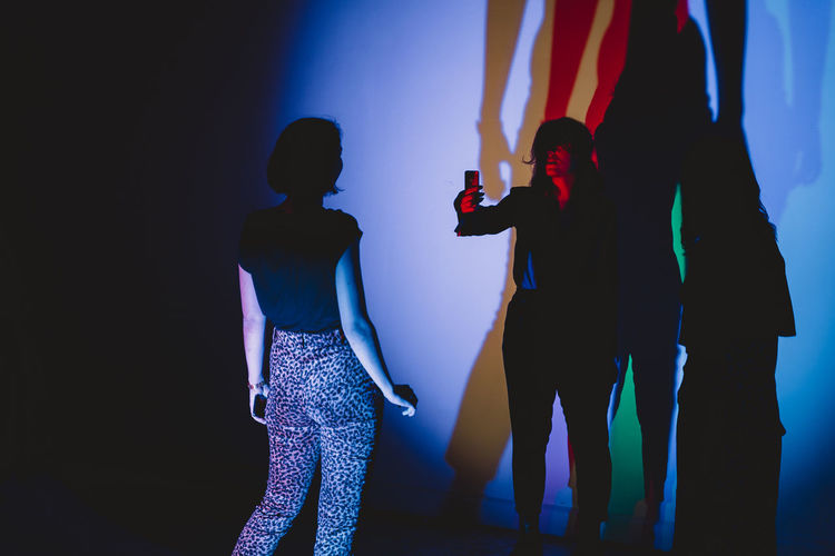 Shadow Games Standing Three Quarter Length Real People Women Indoors  Togetherness Lifestyles Night Illuminated People Adult Nightlife Men Enjoyment Friendship Leisure Activity Blue Dancing