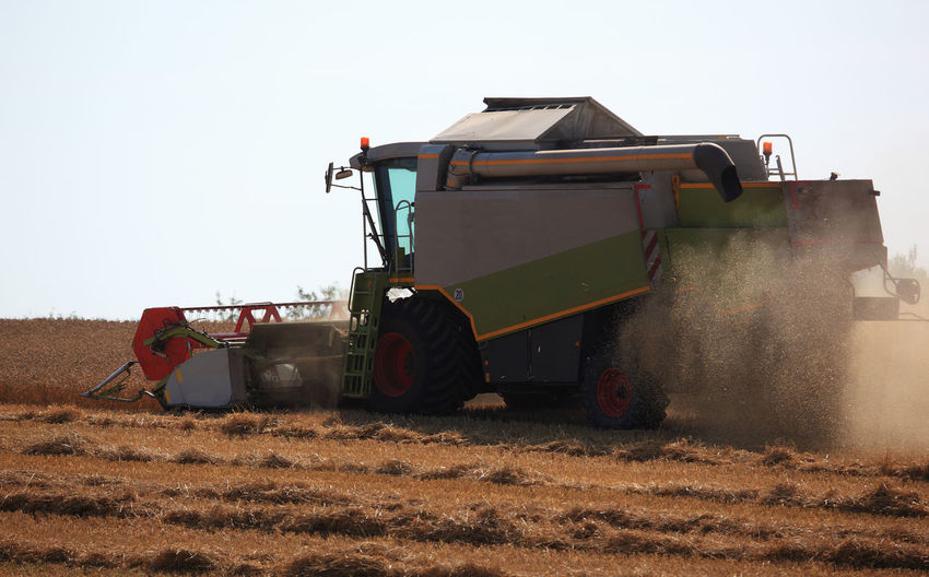 harvester during wheat harvest on a dry dusty field Agricultural Equipment Agricultural Machinery Agriculture Clear Sky Combine Harvester Day Dust Farm Field Harvesting Land Land Vehicle Landscape Machinery Mode Of Transportation Nature No People Outdoors Rural Scene Sky Tractor Transportation