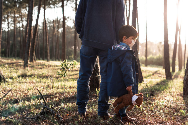 Father and son standing on land in forest