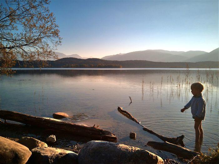 Boy standing on lake against sky