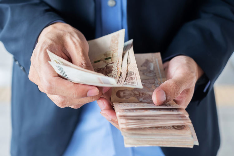 Midsection of businessman counting money