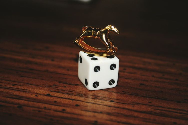 Close-Up Of Dice With Toy On Wooden Table
