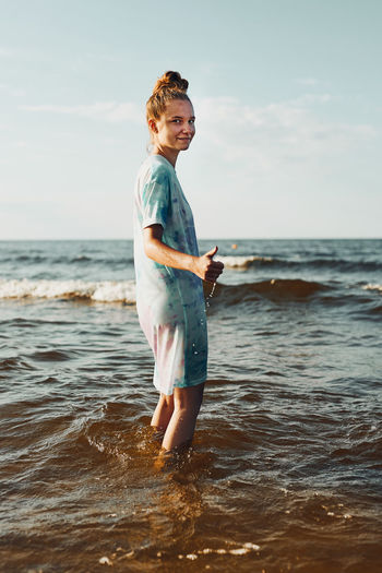 Girl showing okay gesture standing in a water spending a free time over a sea during summer vacation