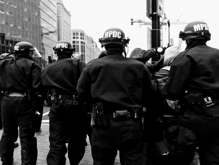 "WASHINGTON, Jan. 20, 2017 -- Police chase #DisruptJ20 marchers during the presidential inauguration of Donald Trump, culminating in a mass arrest of 230 protesters charged with ""felony rioting."" Activism Anarchist Anti-capitalist Anti-Fascist Anti-racist Baton Black Bloc Cops Crowd Control Disrupt J20 District Of Columbia Face Visor Helmet January 20 Protests Journalists Metropolitan Police Department Militarism MPDC Police Officers President Protest Riot Gear Run United States Washington DC"