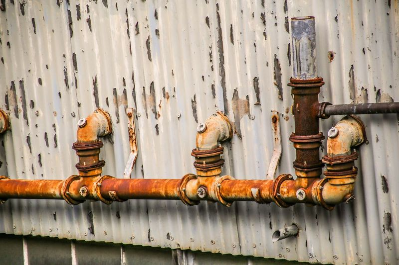 Close-up of rusty pipes on metal wall