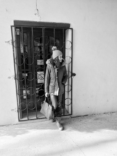 Full length of woman in warm clothing leaning on closed metal gate