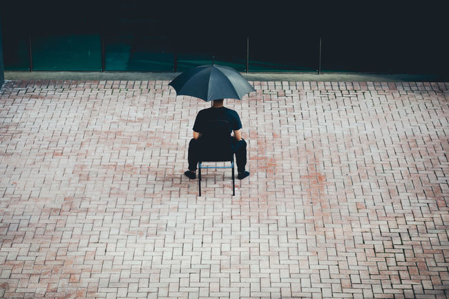 Black Day Full Length Lifestyles Men One Person Outdoors People Real People Sitting Umbrella Under Women Breathing Space