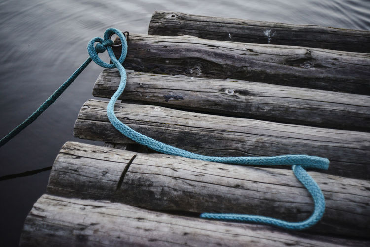 High angle view of blue rope on logs in river