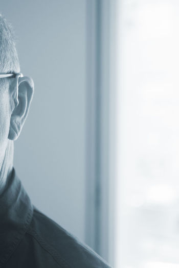 Close-up of man looking at window