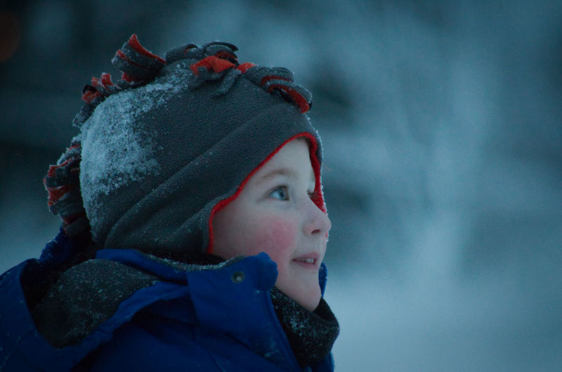Close-up of boy looking away during winter