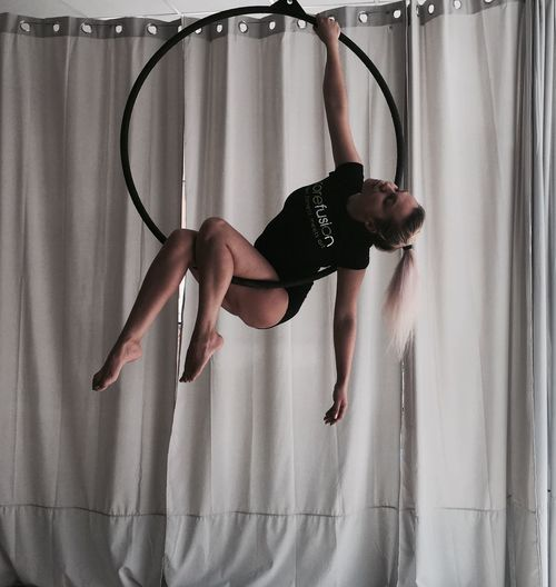 Woman Performing Acrobat On Ring Against Curtain