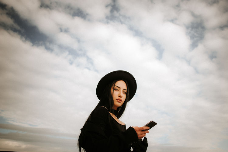 Portrait of beautiful young woman holding mobile phone standing against sky