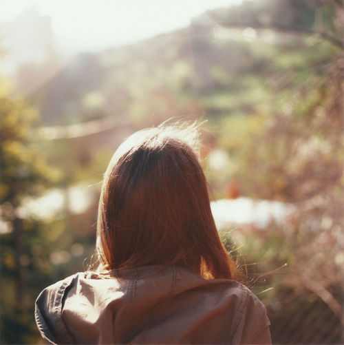 Rear view of woman with brown hair during sunny day