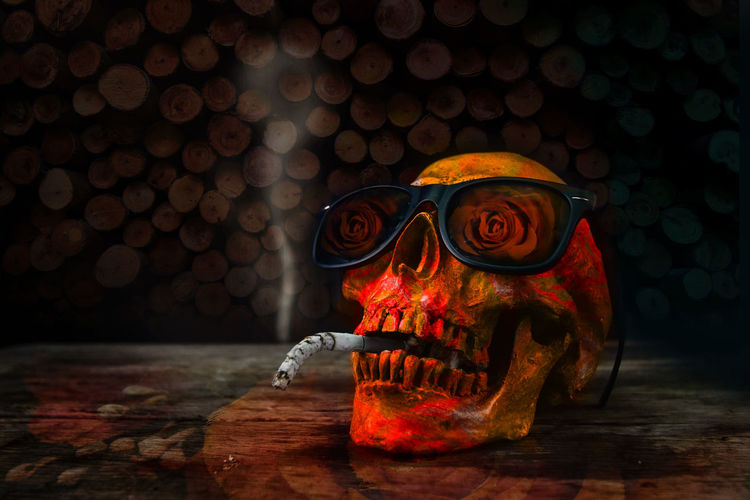 Close-up of human skull with cigarette and sunglasses on table