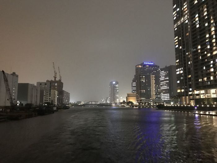River by illuminated buildings against clear sky at night