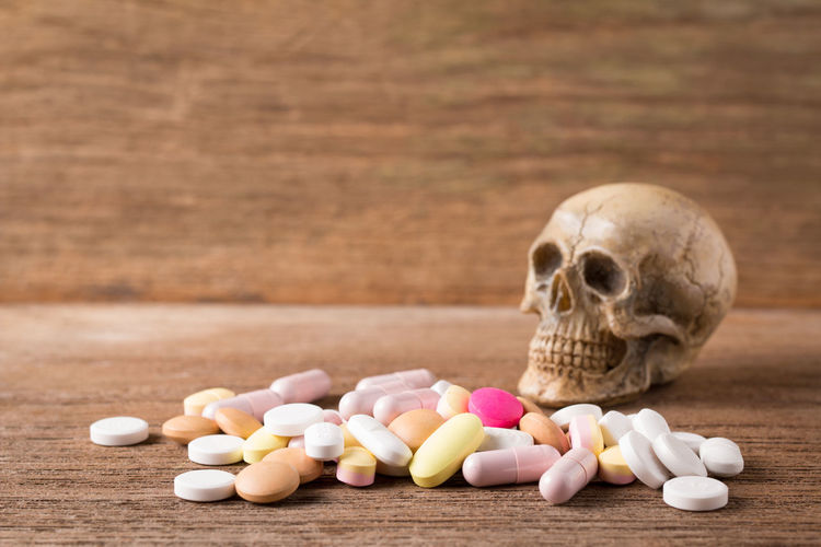 Close-up of human skull and medicines on wooden table
