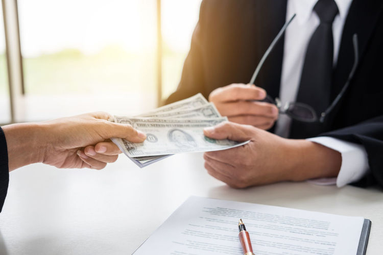 Cropped hand of client giving paper currency to businessman on office desk