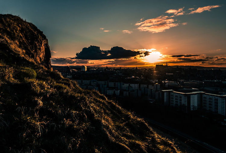 Sunset from above city reflecting on cliff edge