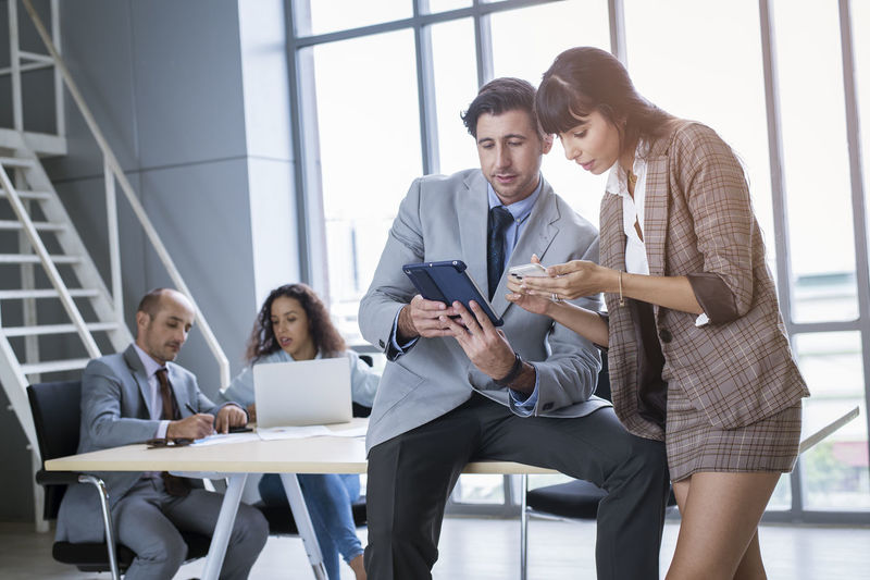People working with mobile phone sitting in office
