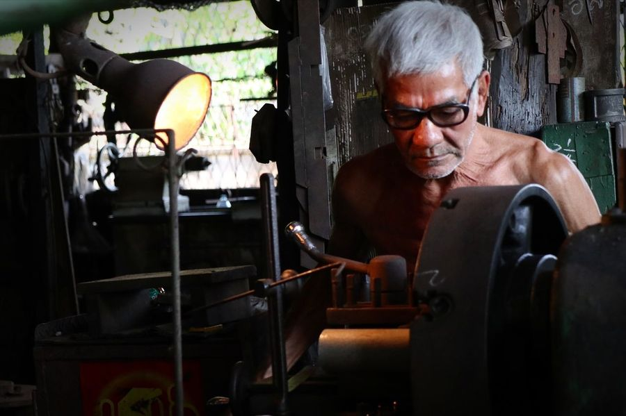 Thailand Blacksmith  Southern Thailand Takuapa Man Older Man Light Light And Shadow White Hair Spotlight EyeEm Selects Eyeglasses  Metal Industry Preparation  Concentration Manufacturing Equipment Blacksmith  Steel Mill Metalwork Molding A Shape Instrument Maker Steel Worker Factory Manufacturing Occupation