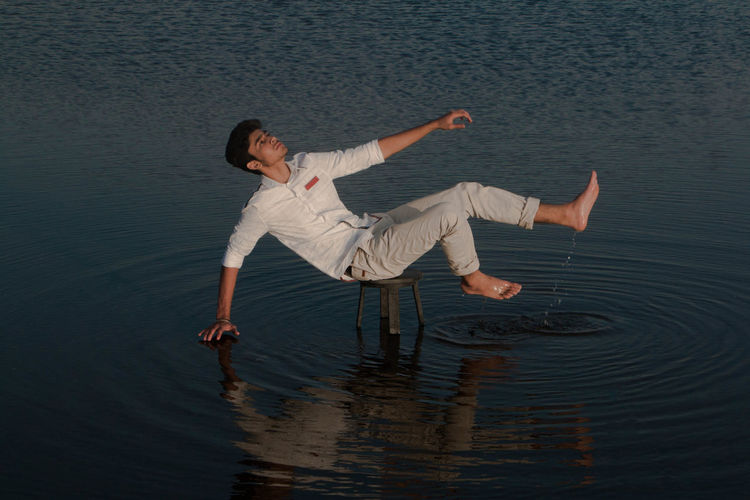 Full length of young man balancing on stool amidst lake