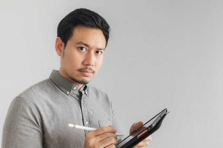 Portrait of man using smart phone against white background