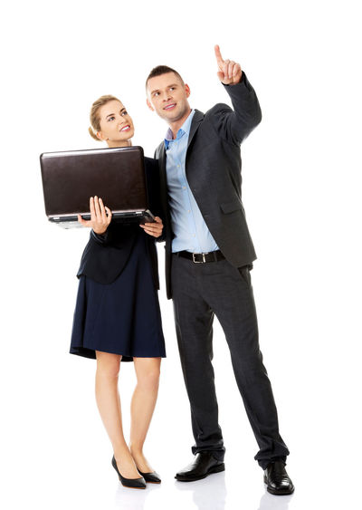 Businesswoman Holding Laptop While Standing By Colleague Against White Background