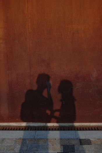 Shadow of man and woman sitting on swimming pool