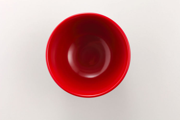 Directly above shot of red tea cup against white background