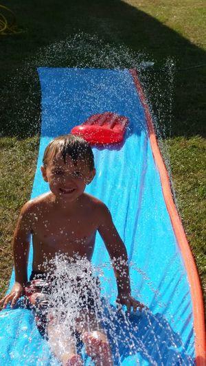 Cute shirtless boy sliding on water slide at backyard