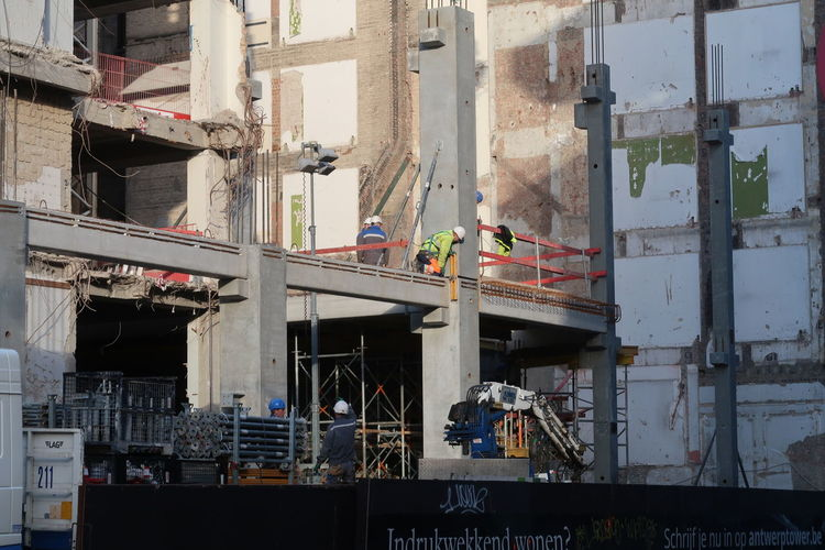 Antwerp, Belgium - December 4, 2018; People working on the construction of the Antwerp tower a skyscraper with appartments being built in the center of Antwerp, Belgium Construction Industry Construction Site Architecture Industry Working Occupation Outdoors Building Construction Worker Real People Built Structure Antwerp Tower Antwerp, Belgium Antwerp Development Building Exterior