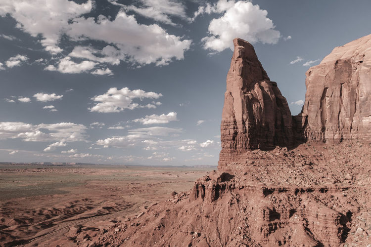 Scenic view of rock formations and landscape against cloudy sky