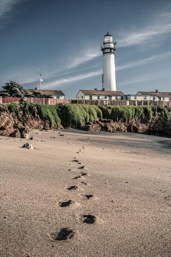 Lighthouse by beach against sky