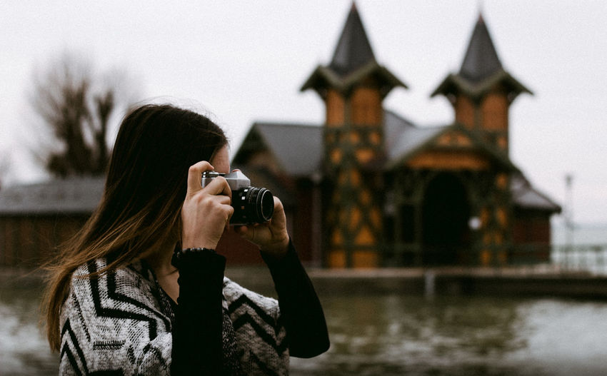 young woman photographing with old vintage zenit camera Photography Themes Photographing Real People One Person Camera - Photographic Equipment Activity Architecture Holding Technology Women Focus On Foreground Lifestyles Water Leisure Activity Built Structure Adult Headshot Photographic Equipment Digital Camera Outdoors Hairstyle Warm Clothing Photographer
