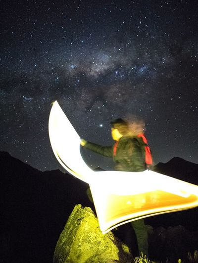 Rear view of person against sky at night