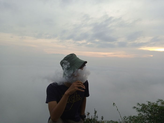Young man smoking while sitting against sky