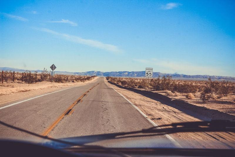 Road amidst fields against sky seen through car windshield