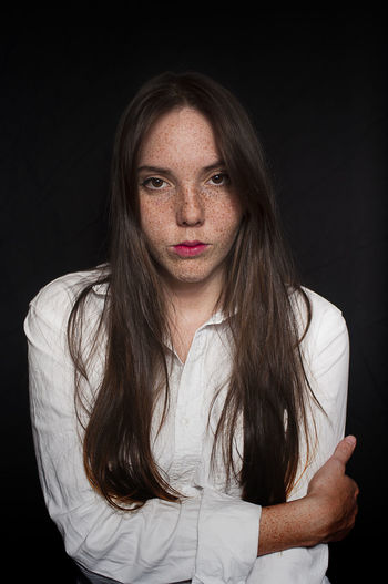 Portrait of woman with freckles against black background