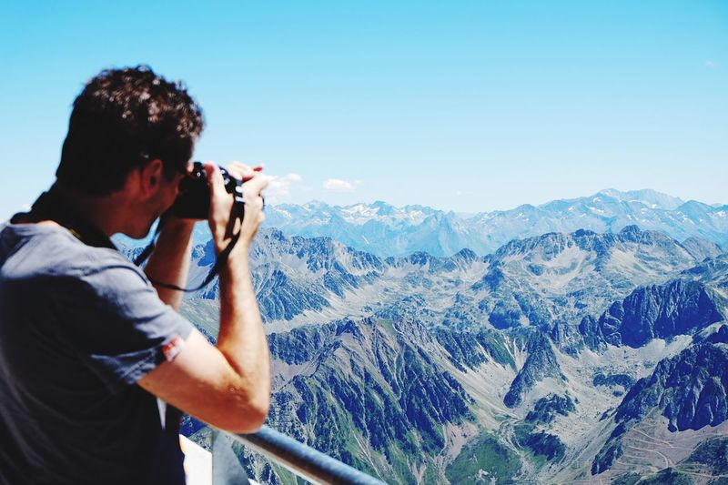 Man photographing mountains against sky at pic du midi de bigorre