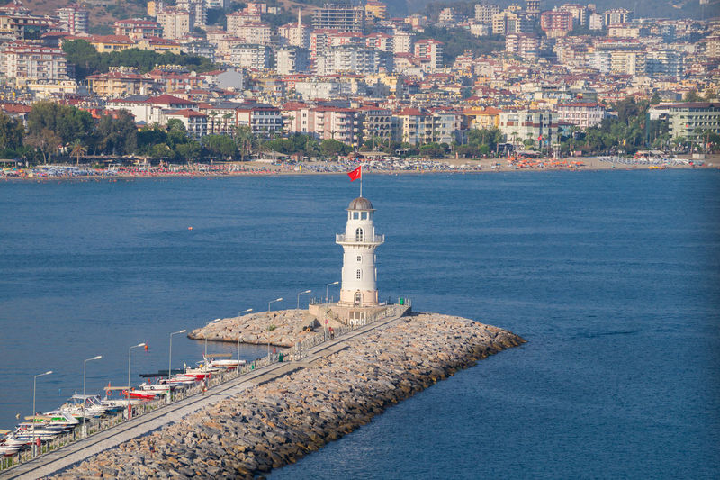 Lighthouse In Sea Against Cityscape