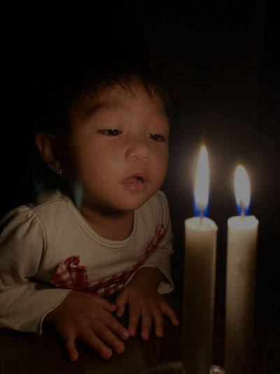 Close-up of cute baby girl in the dark