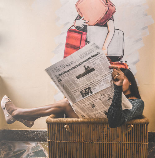 Woman Reading Newspaper While Sitting In Basket At Home
