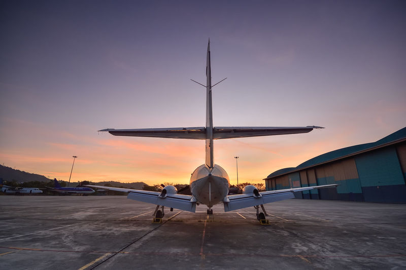 Rear view of airplane on airport runway against sky during sunset