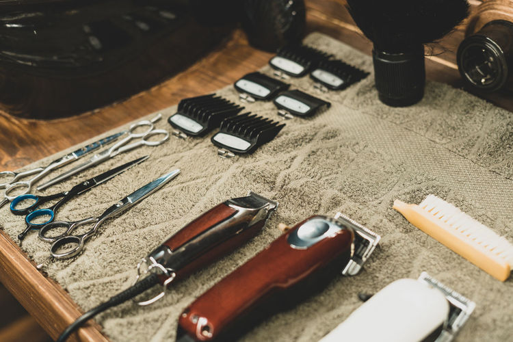 High angle view of hair clippers with scissors at salon