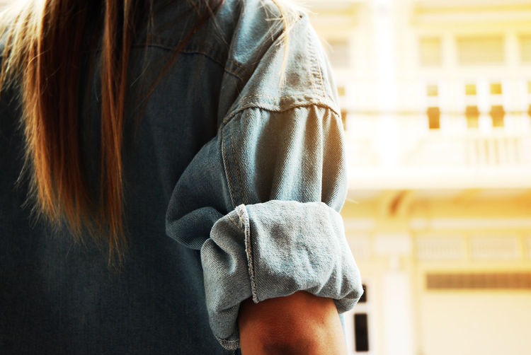 Midsection of woman wearing denim jacket standing against building