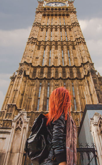 Low angle view of young woman standing against big ben