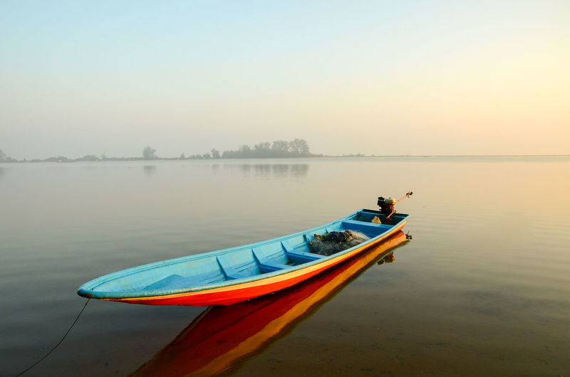 Kayak moored on lake against sky in foggy weather during sunset