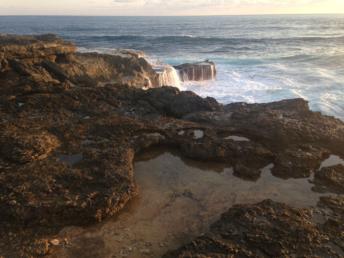 Scenic view of waves splashing on cliff during sunset