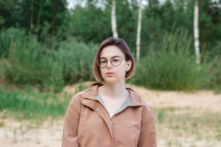 Candid close up portrait of a young woman with short hair in eyeglasses on nature